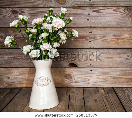 delicate bouquet of carnations in a vase on a vintage wooden background