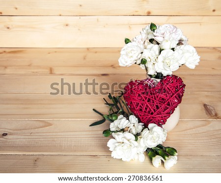 delicate bouquet of carnations in vintage vase with heart on wooden background. Valentine's Day - stock photo