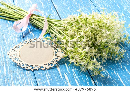 Delicate bouquet of wild orchids, also known as Lesser Butterfly Orchid (Platanthera bifolia) and card for your text on a blue wooden table - stock photo