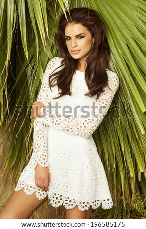 Delicate brunette beautiful woman posing in fashionable white dress, looking at camera. - stock photo