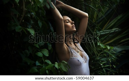 Delicate brunette posing over nature background - stock photo