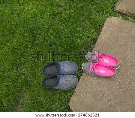 delicate female sneakers and rough garden galoshes - stock photo
