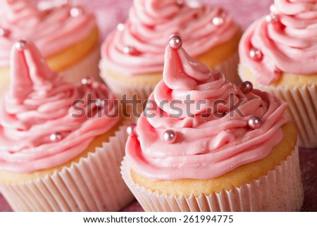 Delicate festive cupcakes with pink cream macro on the table. horizontal  - stock photo
