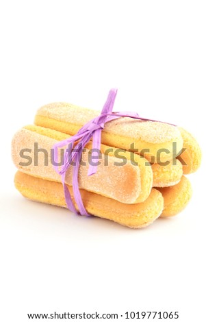 Delicate ladyfinger cookies tied with purple raffia on white background with rom for text