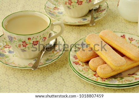 Delicate ladyfinger cookies with tea on pretty china for a springtime treat