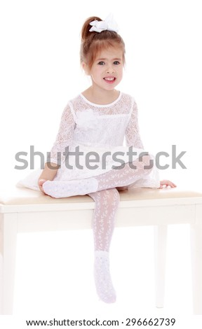Delicate little blonde girl with her hair pulled up into a bun in translucent white short lace dress-white lace tights on a white wooden bench put one leg over the other  - stock photo