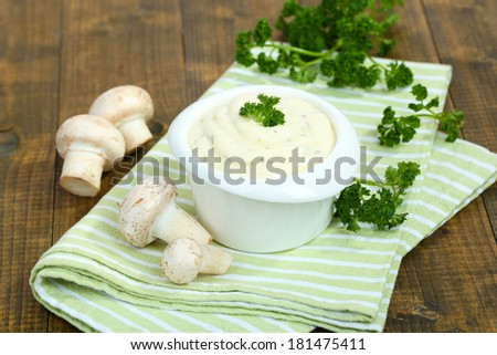 Delicate mushroom sauce in bowl on wooden table close-up - stock photo
