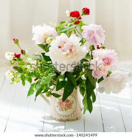 Delicate peonies in a water can standing on the white wooden board - stock photo