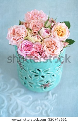 Delicate pink roses in a blue vase on the table. - stock photo