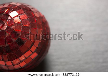 Delicate red mirror Christmas bauble on a dark slate surface - stock photo