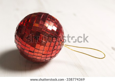 Delicate red mirror Christmas bauble on a light wooden surface - stock photo