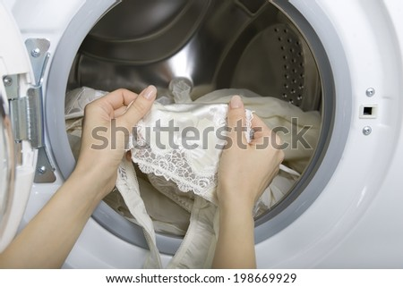 Delicate wash, female hands taking delicate laundry (underwear) from washing machine - stock photo