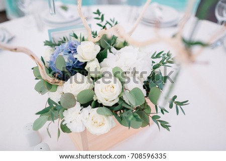 Delicate white roses in a wooden box stand on the table