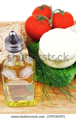 delicatessen cheeses on wooden board with vegetables olive oil and bread isolated over white background - stock photo