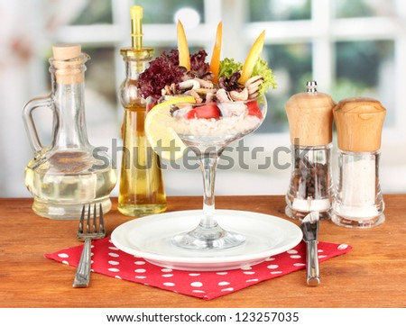 Delicatessen seafood salad with rice in glass on bright background