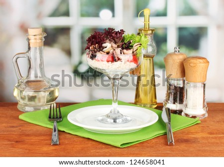 Delicatessen seafood salad with rice in glass on bright background - stock photo
