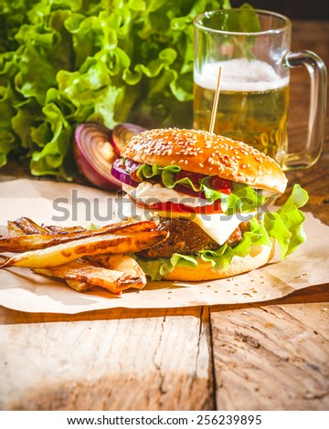 Delicious a burger and fries with a beer in the background onion and lettuce on a wooden rustic table. - stock photo
