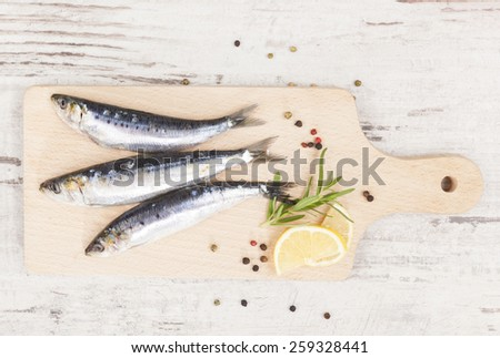 Delicious anchovies fish with peppercorns and fresh herbs on wooden chopping board on white wooden background, top view.. - stock photo