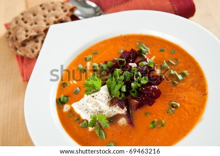 Delicious and Colorful Tomato Soup with Sour Cream, Beets, and Green Onions - stock photo