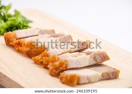 Delicious and crispy deep fried pork belly on cutting board for food on white background  - stock photo