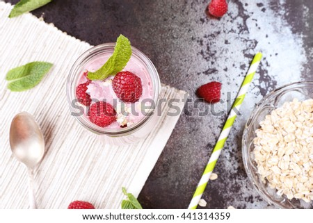 Delicious and healthy breakfast. Berry smoothie yogurt with oat flakes and mint leaves. Jar with milkshake with raspberries, green straw and silver spoon on the table. - stock photo