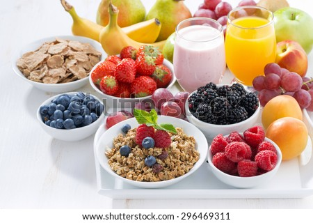Delicious and healthy breakfast with fruits, berries and cereal on wooden tray - stock photo