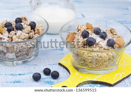 Delicious and healthy granola or muesli with nuts, raisins and berries and jug with milk - stock photo