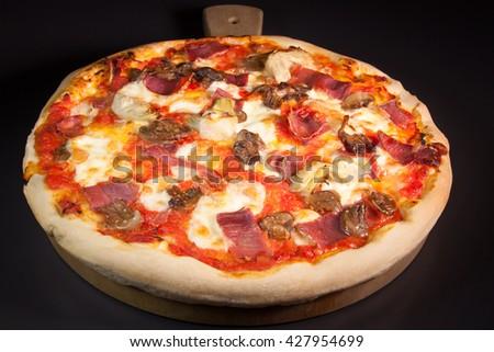 delicious and healthy homemade pizza with mozzarella, ham, mushrooms and artichokes - stock photo