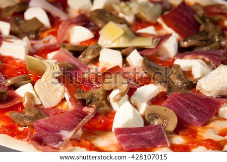 delicious and healthy homemade pizza with mozzarella, ham, mushrooms and artichokes - stock photo