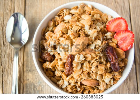 delicious and healthy wholegrain muesli breakfast, with lots of dry fruits, nuts and grains close up, horizontal, on wooden table with spoon - stock photo