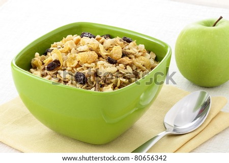 delicious and healthy wholegrain muesli breakfast, with lots of dry fruits, nuts, grains and a fresh apple - stock photo