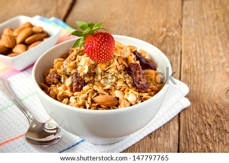 delicious and healthy wholegrain muesli breakfast, with strawberry and lots of dry fruits, nuts (almonds) and grains close up, horizontal, on wooden table with spoon - stock photo