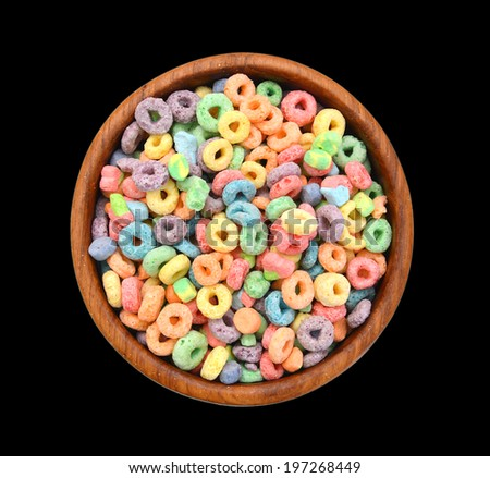 Delicious and nutritious fruit cereal loops flavorful in wooden bowl on black background  - stock photo