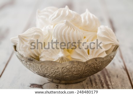 Delicious and plain white vanilla meringue cookies in silver traditional  bowl - stock photo