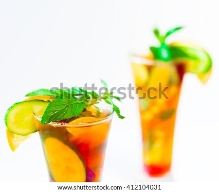 Delicious and tasty alcohol drink cocktail Pimms in the glasses. White background. Bar and Pub concept. Beautiful fruit salad with strawberries. Close up.