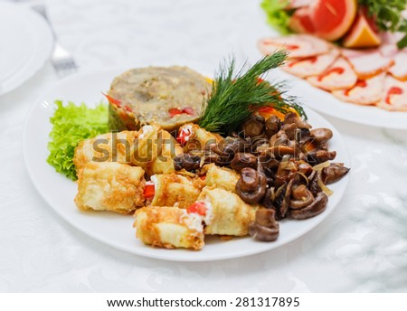 Delicious appetizer close-up. Stuffed zucchini and eggplant salad decorated with mushrooms and greens, vegetarian food - stock photo