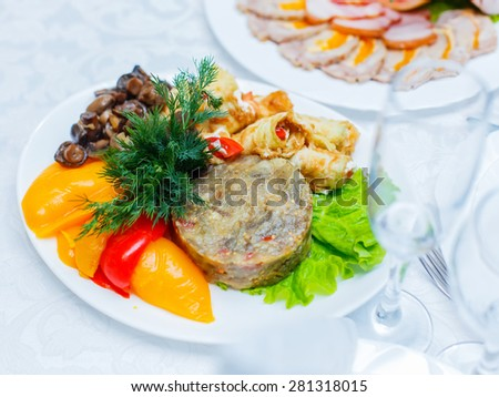 Delicious appetizer close-up. Stuffed zucchini and eggplant salad decorated with mushrooms, peppers and greens, vegetarian food - stock photo