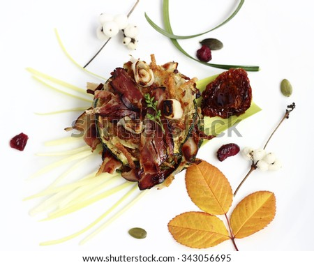 Delicious appetizer with fried potato pancakes, zucchini slices and crispy bacon - stock photo