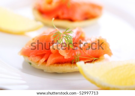 delicious appetizer with salmon pancakes , lemon - stock photo