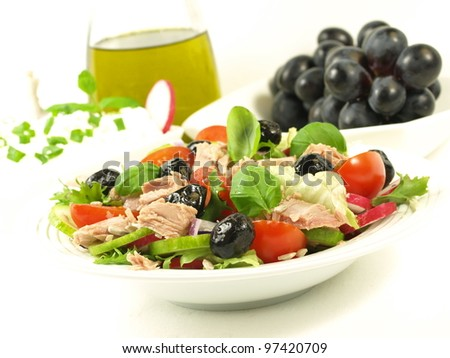 Delicious appetizer with tuna salad, grapes and olive oil in a background - stock photo