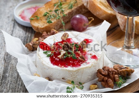 delicious appetizers for wine - camembert, berry jam, toast and fresh grapes, close-up, horizontal - stock photo