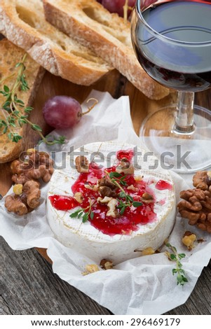 delicious appetizers for wine - camembert, berry jam, toast and fresh grapes, close-up, vertical, top view - stock photo
