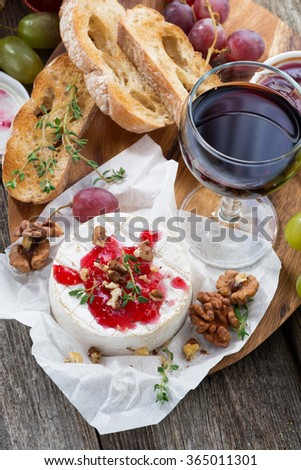 delicious appetizers for wine - camembert, berry jam, toast and fresh grapes, top view, vertical - stock photo