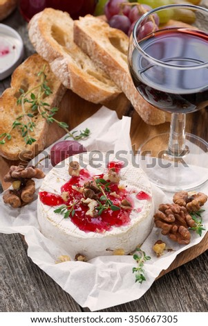 delicious appetizers for wine - camembert, berry jam, toast and fruit, close-up, vertical - stock photo