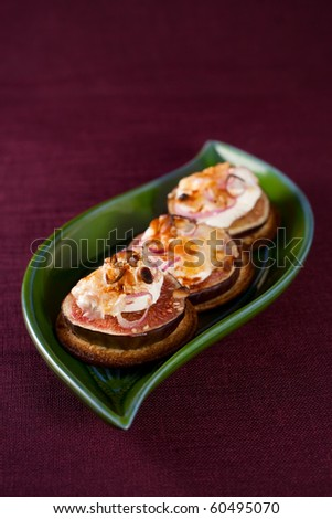 Delicious appetizers topped with goat cheese,fig,nut and sweet onion - stock photo