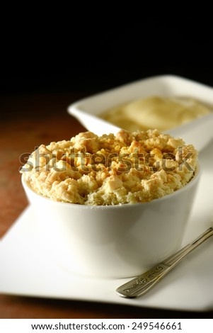 Delicious apple crumble in a white ramekin with Devon custard in background. Copy space.  - stock photo