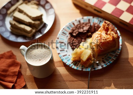 Delicious Apple pie, a cup of cocoa, halva and chess with soft sunlight. - stock photo