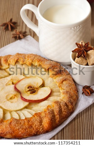 Delicious apple pie with spices and mug of milk.