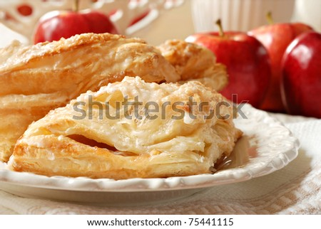 Delicious apple turnovers on decorative plate with fresh gala apples in background.  Closeup with shallow dof. - stock photo