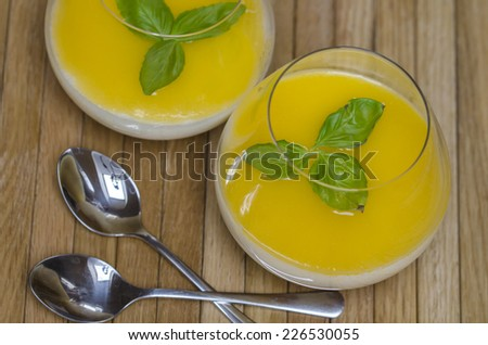 Delicious apricot dessert with chocolate cream and mint leaves with two spoons
